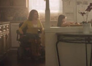A woman in a motorized wheelchair teaches her young niece how to use the microwave to make snacks.